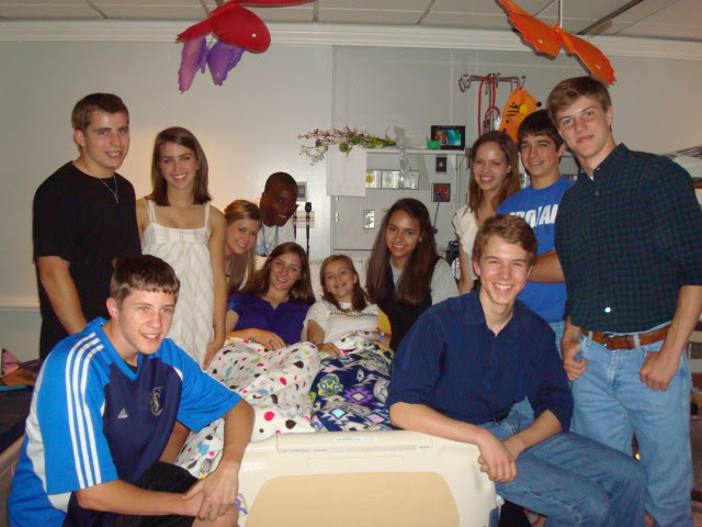 Carley Rutledge sitting on a hospital bed, surrounded by her friends